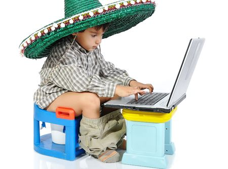 potty: Cute kid with mexican hat on head, sitting on toilet with laptop