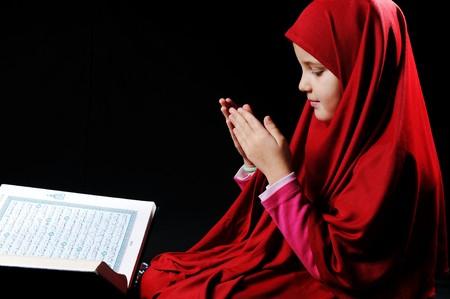learning pray: Muslim girl with Holy Book Koran Stock Photo