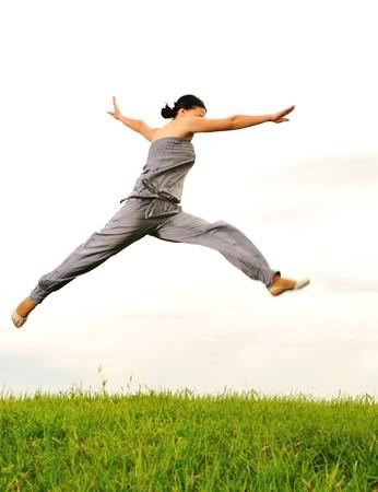 Happy acrobatic girl on meadow photo