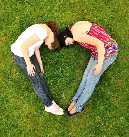 Two girl making a shape of heart photo