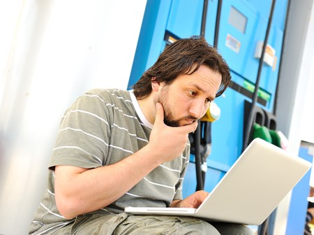 benzine: Man with laptop on gas station with silly expression on his face after reading last news Stock Photo