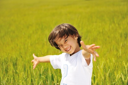 widely: Happy kid on green field with widely opened arms
