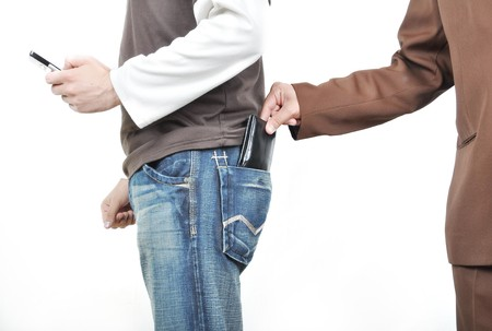 The male hand pulls out a purse from a pocket of the man. photo