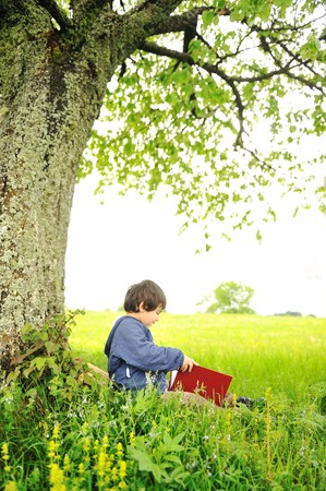 Happy children reading the book under the tree photo