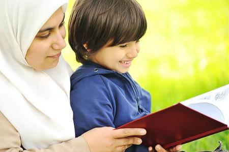 mujeres musulmanas: La madre de musulmanes y su hijo en la naturaleza, leyendo juntos  Foto de archivo