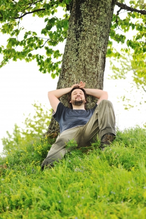 rest and relaxation: Happy young man resting under the tree