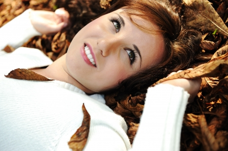 Close-up portrait of an beautiful autumn woman laying on ground Stock Photo - 8084455