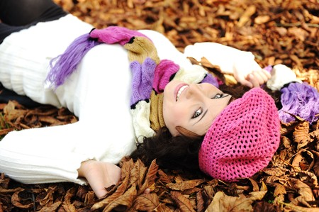 Close-up portrait of an beautiful autumn woman laying on fall leafs Stock Photo - 8084461