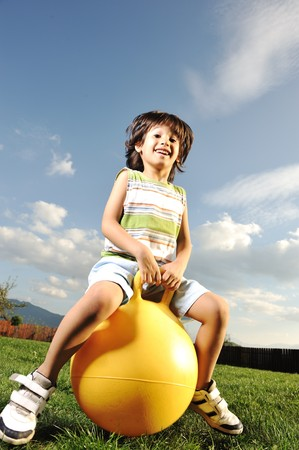 balls kids: Little happy boy playing with big ball and jumping with slight motion up, scene in park Stock Photo