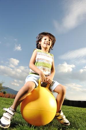 enfants qui rient: Petit gar�on heureux jouant avec big ball et le saut avec l�ger mouvement up, sc�ne dans le parc