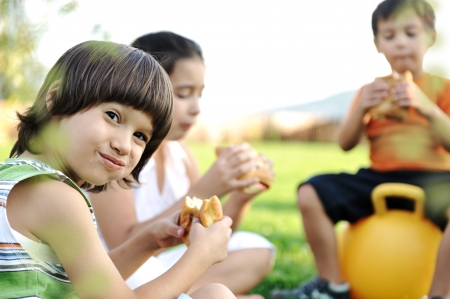 trois enfants: Trois enfants dans la nature joue et manger ensemble