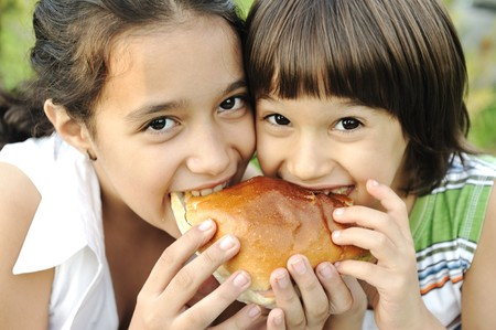 Closeup of two children eating sandwich in nature together, healthy food, care and love Stock Photo