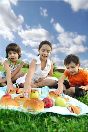 ni�os comiendo: Peque�o grupo de ni�os comiendo juntos en la naturaleza, picnic, bella escena