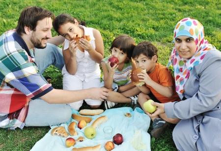 femmes muslim: Famille musulmane, m�re et p�re de trois enfants ensemble dans la nature et de manger assis sur l'herbe verte: pique-nique