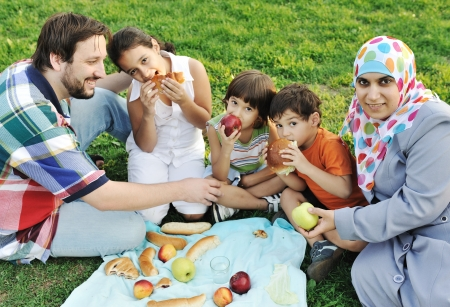 muslims: Muslim family, mother and father with three children together in nature sitting and eating on green grass: picnic