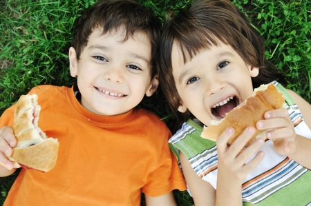 Two cute boys laying on ground in nature and happily eating healthy food  Stock Photo