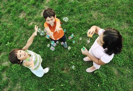 pompas de jabon: Peque�o grupo de ni�os felices haciendo burbujas y tocar juntos en la naturaleza