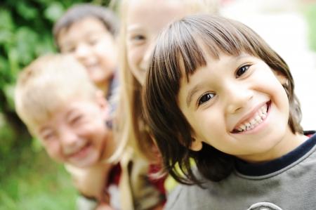 ni�os contentos: Felicidad sin l�mite, los ni�os felices juntos al aire libre, caras, sonrientes y descuidados  Foto de archivo