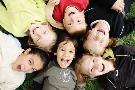 ni�os riendose: Felicidad sin l�mite, feliz grupo de ni�os en c�rculo, junto al aire libre, caras, sonrientes y descuidados  Foto de archivo
