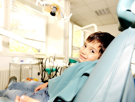 heal care: At dentists modern working place, cute kid sitting on chair and smiling Stock Photo