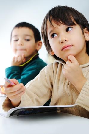 wiedererkennen: Zwei cute Schule Jungen gemeinsam auf Ihre Hausaufgaben und einer von Ihnen Cheeting
