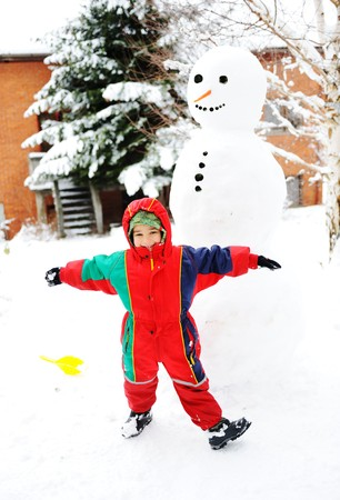 Kid playing happily in snow making snowman, winter season photo