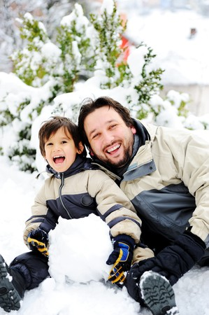 Father and son playing happily in snow making snowman, winter season photo