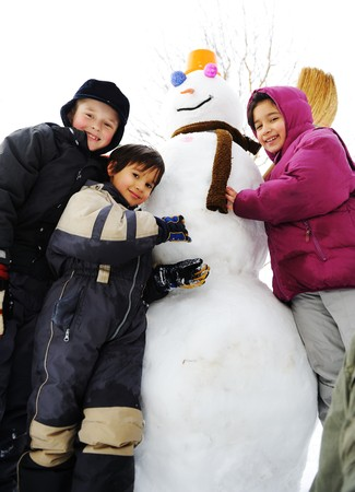 Group of children playing happily in snow making snowman, winter season photo