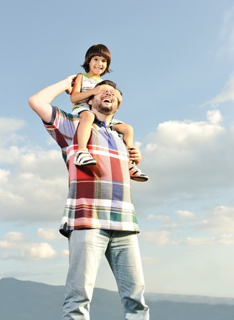 Young father and his son on back, piggyback, pikaboo playing, outdoor scene, love and care photo