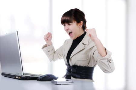 Excited young business woman with her clenched fist photo