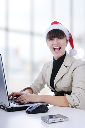 Pretty female wearing santa hat, holding organiser, using mobile, smiling in office photo