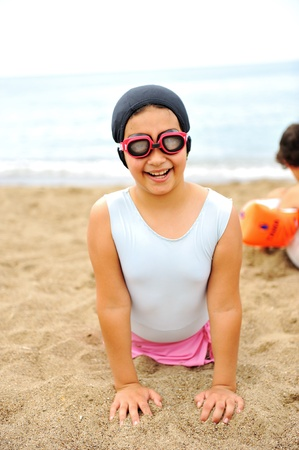 Kid on beach in sand playing, people around, summer hot nice time photo