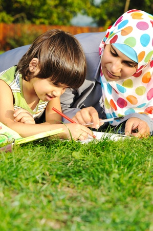 Mother and child learning in nature, Muslim eastern traditional clothes Stock Photo