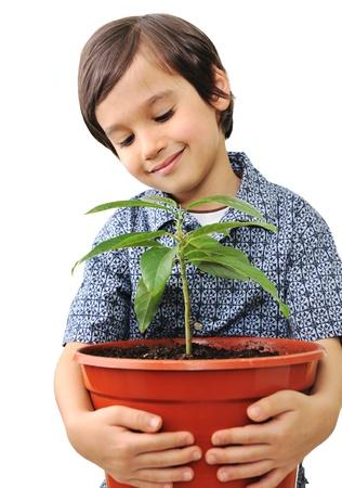 Closeup portrait of a beautiful happy little child holding plant photo
