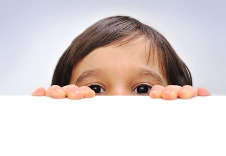 Child holding ein leeres Zeichen über einen weißen Hintergrund, versteckt sich hinter Standard-Bild