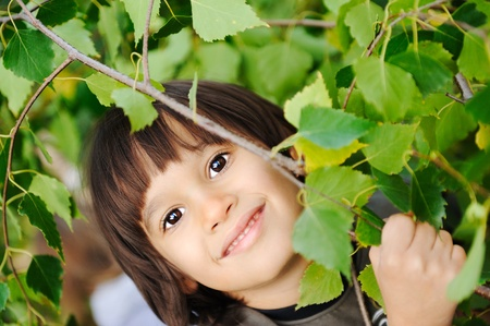 Kid playing in trees and bushes  photo