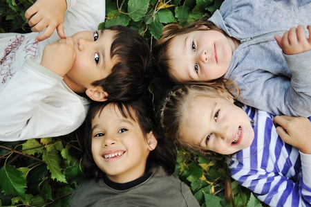 lying in leaves: kids in circle  Stock Photo