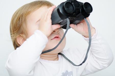 Baby with binoculars, closeup photo