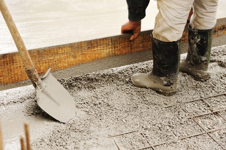 work material: Man leveling concrete slab Stock Photo
