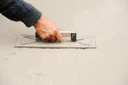Construction worker spreading wet concrete photo