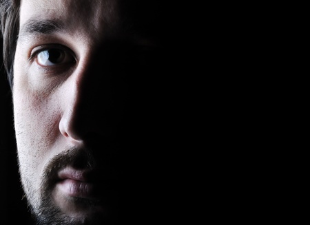 scary face: Low-key portrait - half face - sad and angry looking man