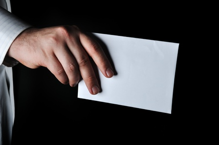 secrecy of voting: Hand holding a white envelope with dark background
