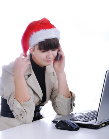 Beautiful business woman is working in office in santa claus hat - talking on cell phone photo