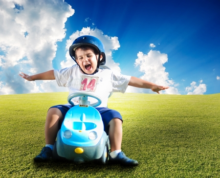Driving a car: Happy kid on green meadow driving a car Stock Photo