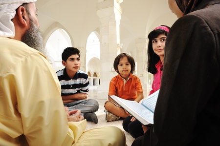 learning arabic: Islamic education inside white mosque, teacher and children learning together (or mother and father with them)