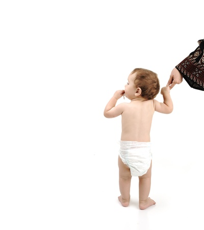 baby with diaper learning to walk with help of his mother, isolated with large copy-space for your message photo