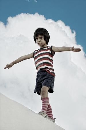 Kid walking and balancing on wall photo