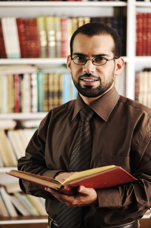 arab people: Young happy man standing in university library reading and smiling