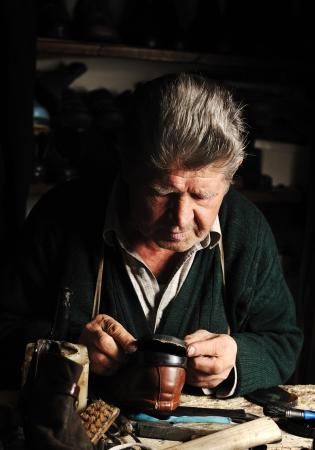 cobbler: Old man, shoemaker, repairing old handmade shoe in his workshop