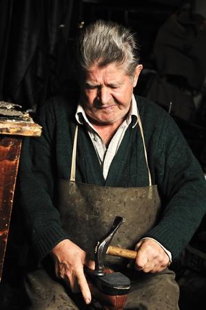 pinafore: Elderly man, shoemaker repairing old shoe in his workshop